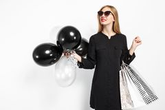 Elegant woman wearing sunglasses in a black dress and red lips, stock photo