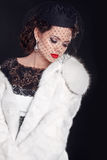 Elegant woman wearing in white fur coat isolated on black backgr royalty free stock photos