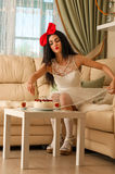 Elegant woman in a white dress doll takes the cake with cherries Stock Images