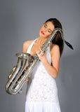Elegant woman in white dress holding saxophone Royalty Free Stock Photos