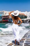 Elegant woman  enjoys the view to Little Venice in Mykonos. Elegant woman in white enjoys the view to Little Venice in Mykonos, Greece Royalty Free Stock Images