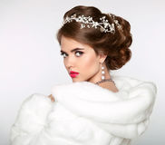 Elegant woman in white fur coat. Wedding Hairstyle. Beautiful fa Stock Photography