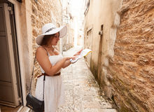 Elegant woman in white hat looking at paper map on old narrow st Stock Image