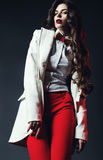 Elegant woman in white shirt with bow tie and in red pants Royalty Free Stock Images
