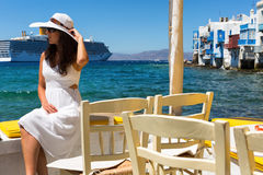 Elegant woman in white sits at the waterfront of Little Venice in Mykonos, Greece. Elegant woman in white dress and white hat sits at the waterfront of Little Stock Photography