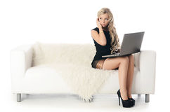 Elegant woman on a white sofa with the laptop. Business conc Stock Photos