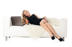 The elegant woman on a white sofa with the laptop Royalty Free Stock Photos