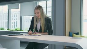 Elegant woman working in stylish office. Modern blond woman in trendy suit sitting at table in light contemporary office. Modern blond woman in trendy suit stock video