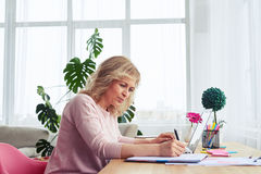 Elegant woman writing while working Royalty Free Stock Photography
