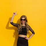 Elegant Woman On Yellow Background Pointing Up Royalty Free Stock Images