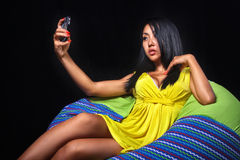 Elegant woman in a yellow dress posing lying on bean bag on a black background Royalty Free Stock Photo