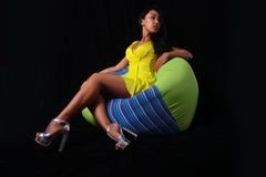 Elegant woman in a yellow dress posing lying on bean bag on a black background Royalty Free Stock Photography
