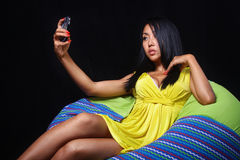 Elegant woman in a yellow dress posing lying on bean bag on a black background Stock Photography