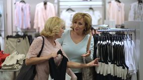 Elegant women looking for dress in clothing store stock video