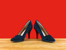 Elegant women's shoes. Elegant black women's shoes in front of a red wall Stock Images