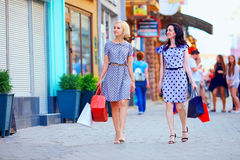 Elegant women walking colorful city street Stock Images