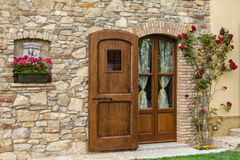 Elegant wooden door. An elegant wooden door of a countryside house surrounded by nice flowers royalty free stock image