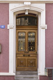 Elegant wooden door and red wall. An elegant wooden door of a mauve painted mansion in the city of Basel, Switzerland Stock Photo