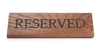 Elegant wooden sign RESERVED on white background. Table setting element stock photography