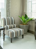 Elegant woonkamerbinnenland met gestreepte patroonhoofdkussens op leunstoel Stock Afbeeldingen