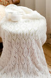 Elegant woven handicraft knit white sweater, jumper or cardigan closeup detail. Detail of woven hand made knitting woolen design texture and clew. Fabric white stock photo