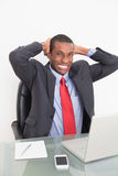 Elegant young Afro businessman with laptop at desk Stock Image