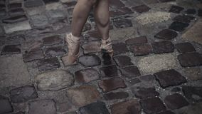 Elegant young ballet dancer medieval street under the rain. Stepping on tip toes in pointe. Close up of a ballerina`s stock footage