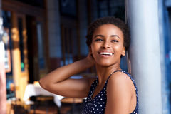 Elegant young black woman smiling outside. Side portrait of elegant young black woman smiling outside Royalty Free Stock Photography