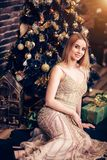 Elegant young blonde woman in a long evening Golden dress sitting near the Christmas tree and smiling royalty free stock photography