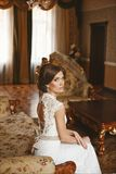 Elegant young bride with beautiful blue eyes and with wedding hairstyle in the stylish dress with lace sits on the stock images