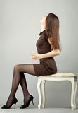 Elegant young brunette sitting on a banquette Royalty Free Stock Photo
