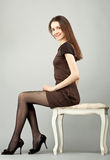 Elegant young brunette sitting on a banquette Stock Photos