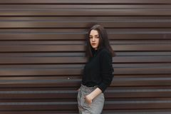 Elegant young brunette woman with natural make-up in a black vintage sweater in checkered pants stands on a warm spring day. Near a metal wall outdoors. Urban royalty free stock images