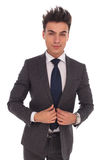 Elegant young business man buttoning his coat Royalty Free Stock Image