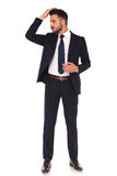 Elegant young business man fixing his hair style. On white background royalty free stock photo