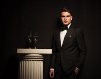 Elegant young business man leaning on a black wall Royalty Free Stock Photo