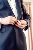 Elegant young business man in tuxedo buttoning the Royalty Free Stock Photos