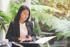 Elegant young business woman looking at document summary and using smartphone for calculator business income Stock Image
