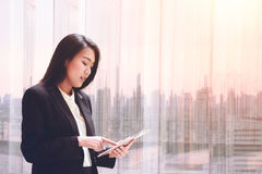 Elegant young business woman using tablet by the window for relax, looking at screen and Business District blurred Stock Photo