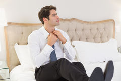Elegant young businessman adjusting tie in bed Royalty Free Stock Photography
