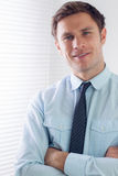 Elegant young businessman with arms crossed in office Stock Photos