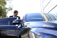 Elegant young businessman entering his comfortable car while standing outdoors stock image