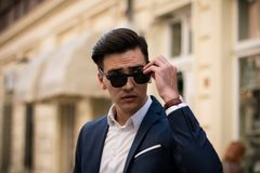 Elegant young businessman with sunglasses outdoors royalty free stock photos
