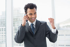 Elegant young businessman using cellphone in office Royalty Free Stock Photography