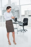 Elegant young businesswoman with clipboard in office Royalty Free Stock Photo