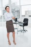 Elegant young businesswoman with clipboard in office Royalty Free Stock Photography