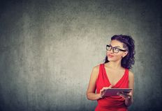Elegant young businesswoman in red dress using tablet Royalty Free Stock Photography