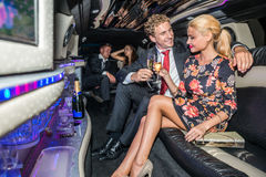 Elegant young couple toasting champagne flutes in limousine Royalty Free Stock Photo
