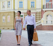 Elegant young couple on vacation. Walking hand in hand along a sidewalk in an affluent urban environment Royalty Free Stock Image