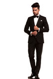 Elegant young fashion man adjusting his tuxedo Royalty Free Stock Photography